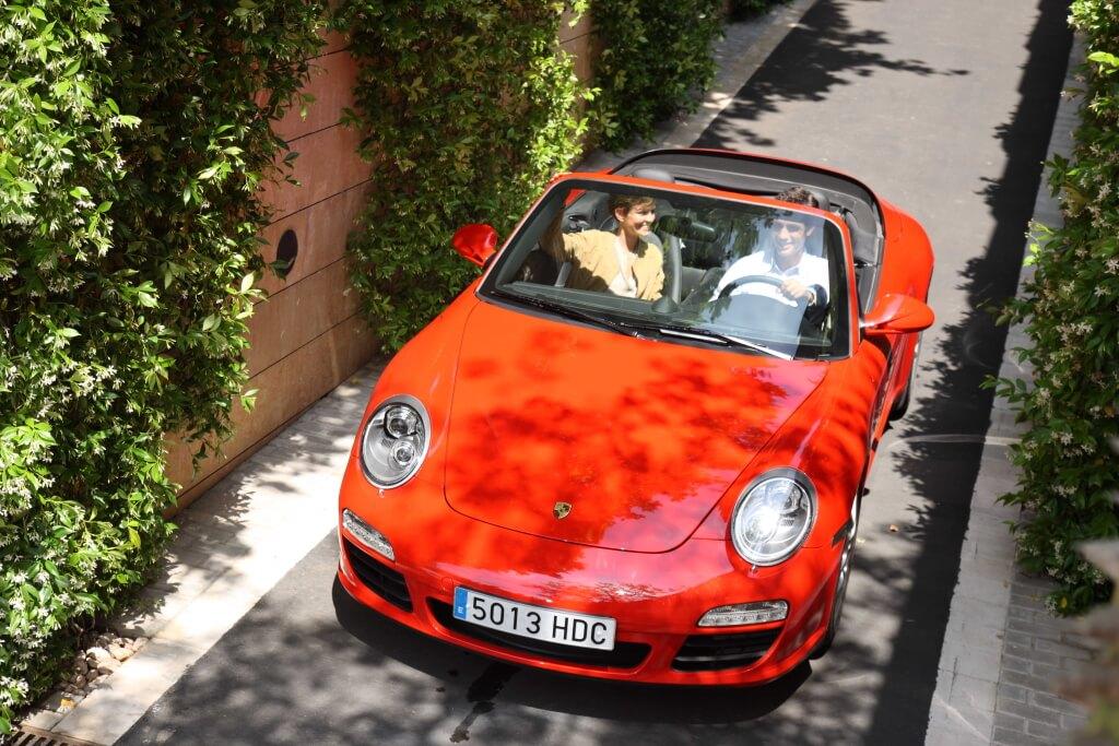 Pisos de lujo en Barcelona, pareja saliendo del parking de One Pedralbes House conduciendo un deportivo marca Porsche.